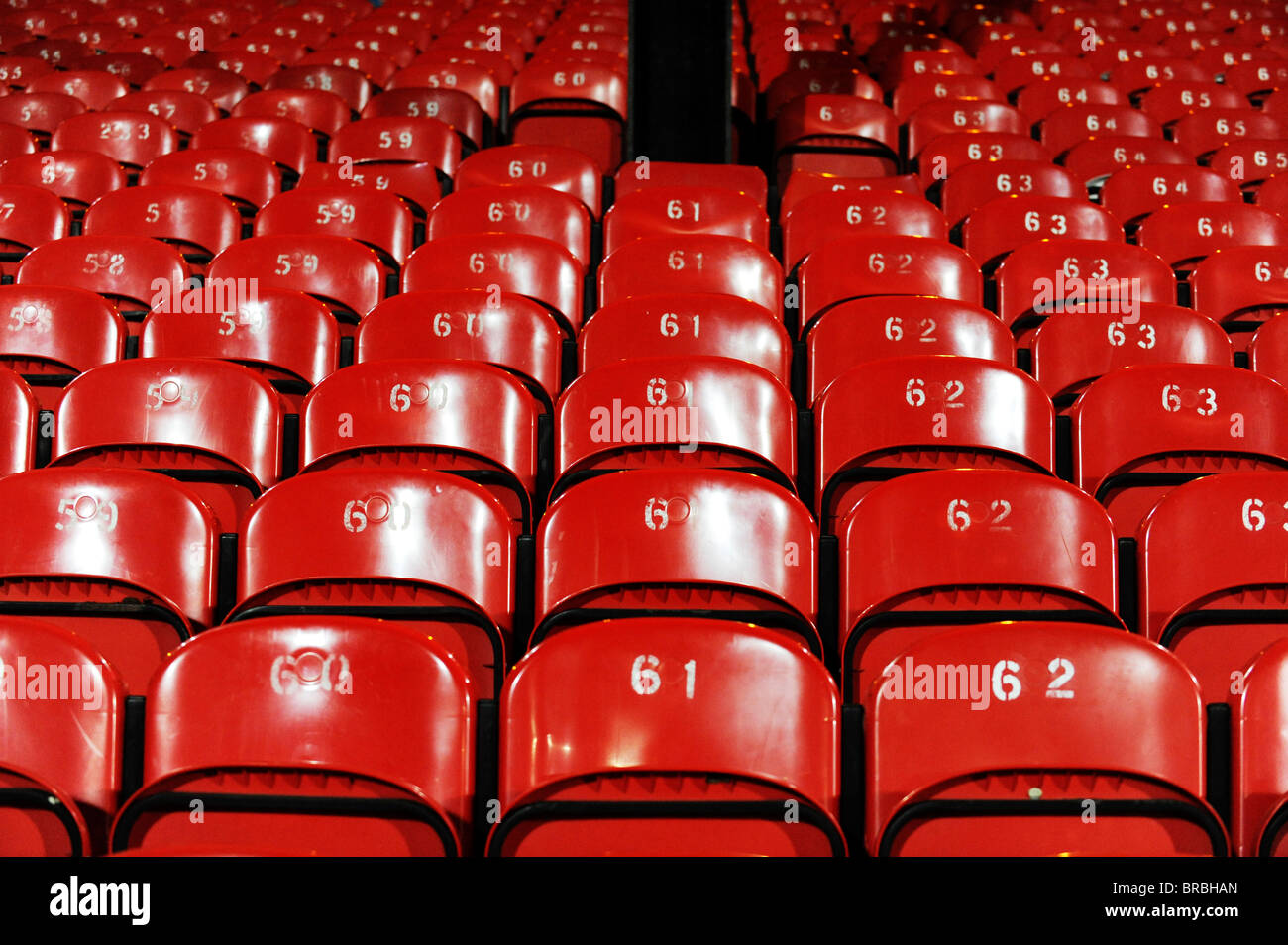 Red seats at a sports stadium. - Stock Image