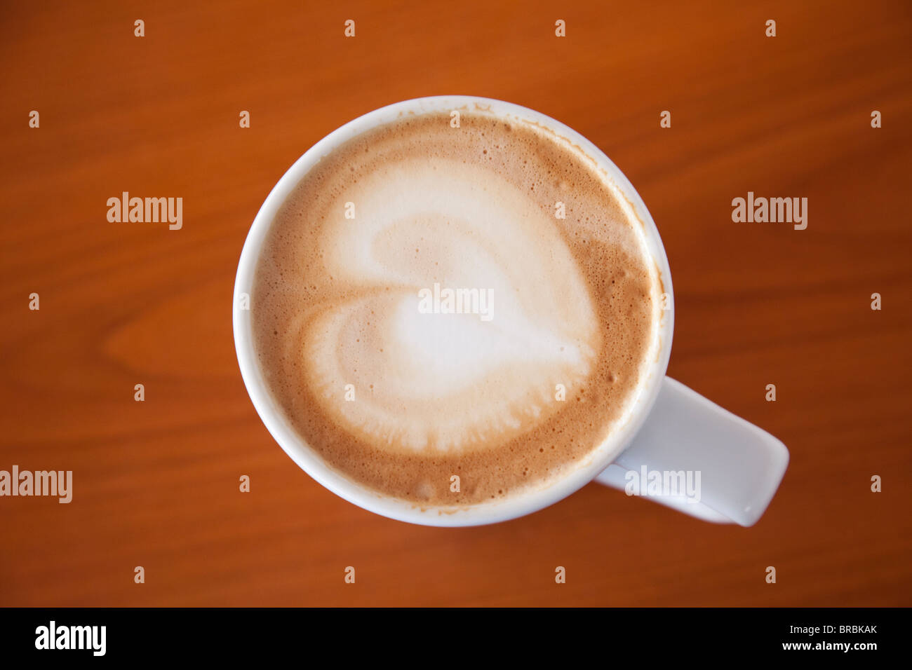 Top down of a mug of cafe Latte coffee with a heart shape in froth on top of a wooden table background from above. - Stock Image