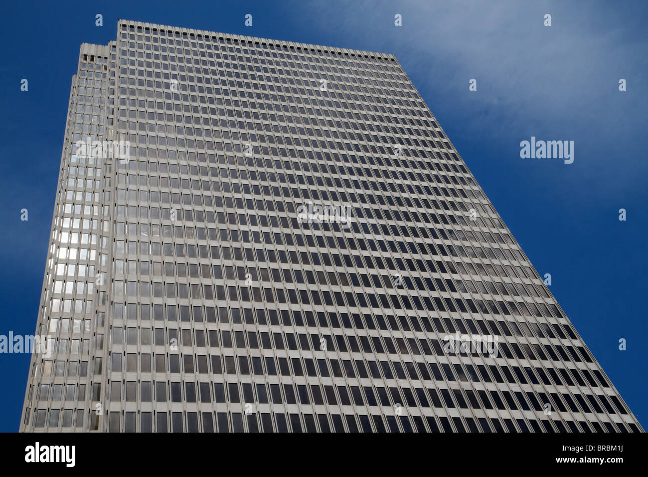 Skyscraper with blue sky background and reflections of clouds - Stock Image