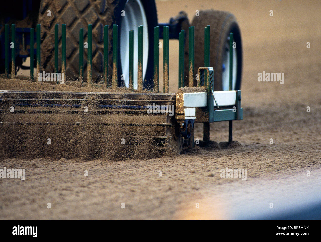 Tractor pulls a grooming machine across a horse racing track Stock Photo