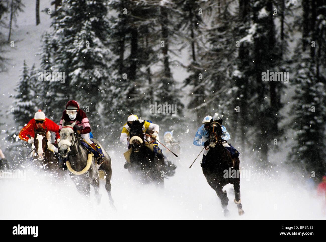 Group of horses and jockeys in masks and hardhats take corner towards the finish line - Stock Image