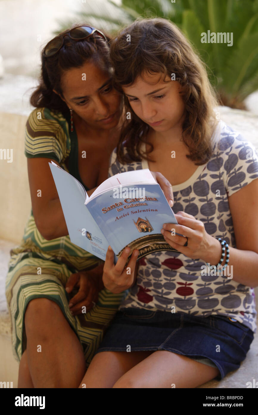 Mother and daughter reading a guide book, Galatina, Lecce, Italy - Stock Image