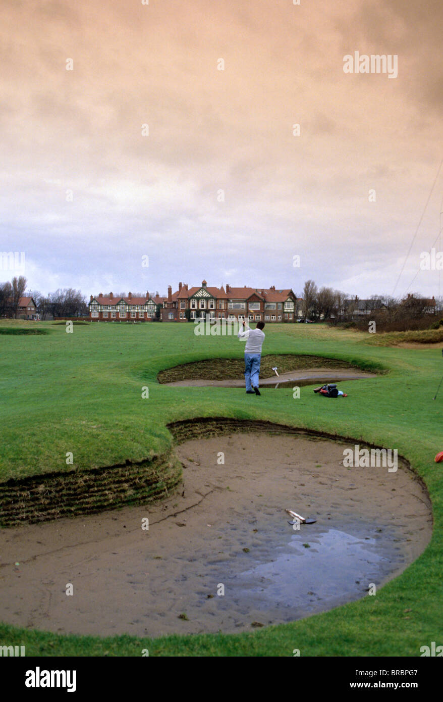 Golfer plays his approach shot from between two sodden sand bunkers - Stock Image