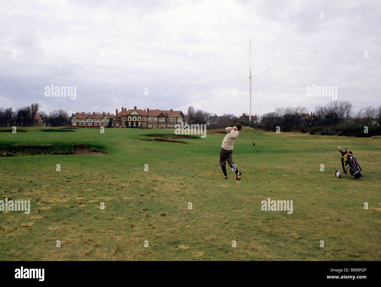 Golfer in plus-fours hits a long approach shot to the green - Stock Image