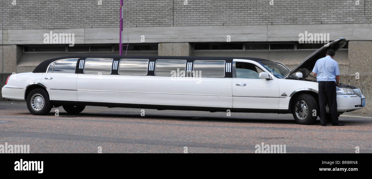 Driver of stretch limo checking under raised bonnet hood - Stock Image