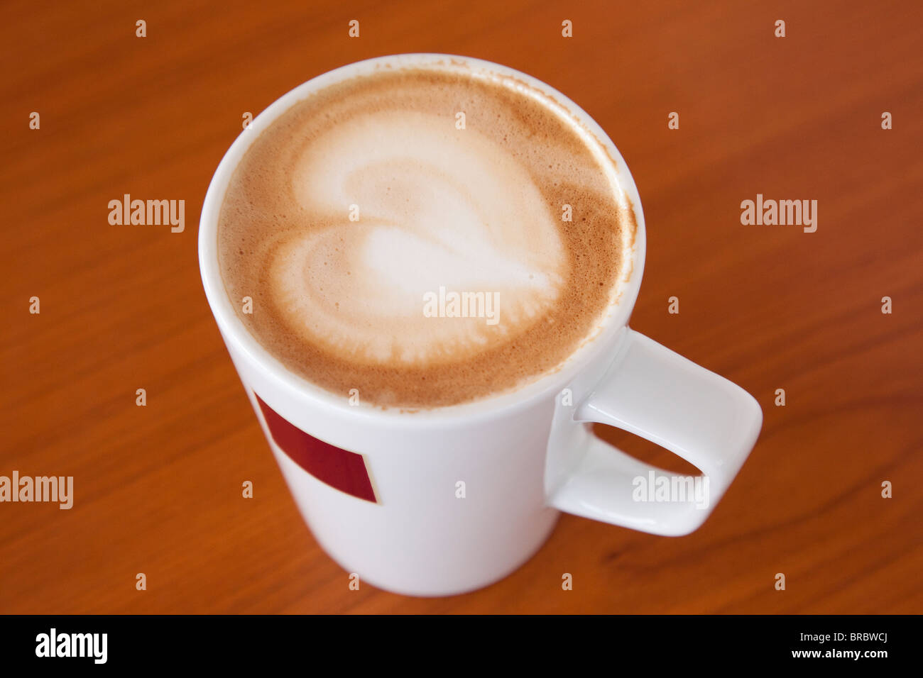 Mug cup of cafe Latte coffee with a heart shape in the froth on top of a brown wooden table from above. England, - Stock Image