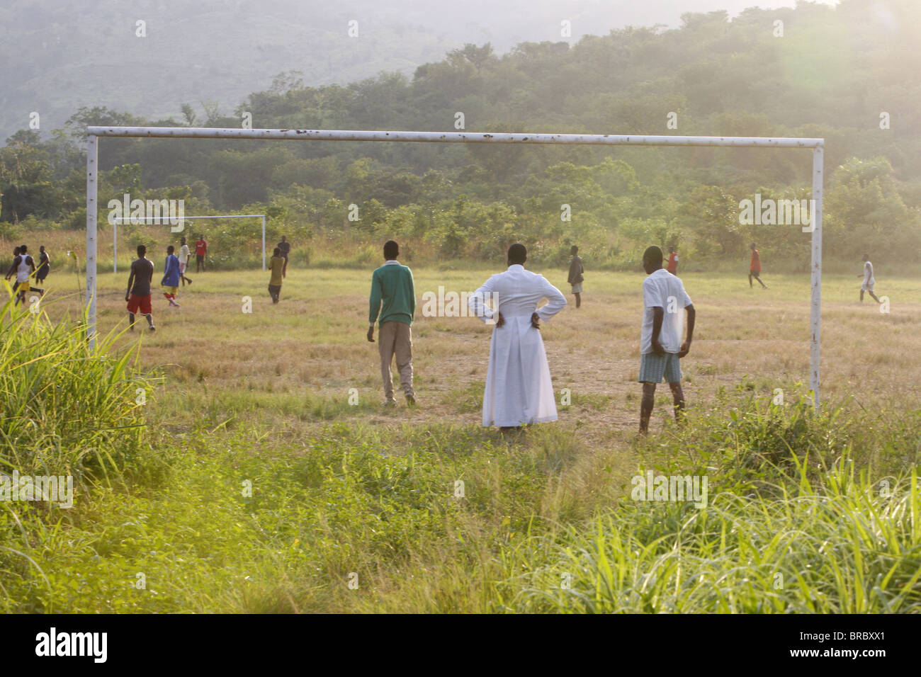 Catholic priest watching a soccer game, Akata Djokpe, Togo, West Africa Stock Photo