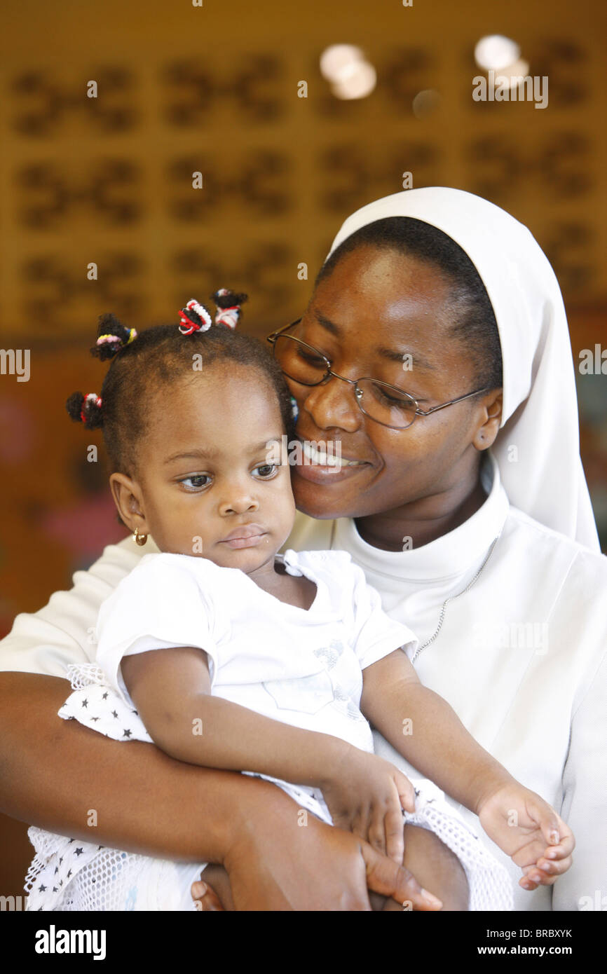 Franciscan sister holding an orphan at nursery and kindergarten run by Catholic nuns, Lome, Togo, West Africa - Stock Image