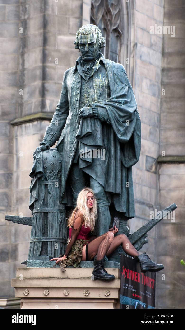 Street performer at the Edinburgh Fringe Festival sitting at the bottom of a statue, Edinburgh, Scotland, UK, Western - Stock Image