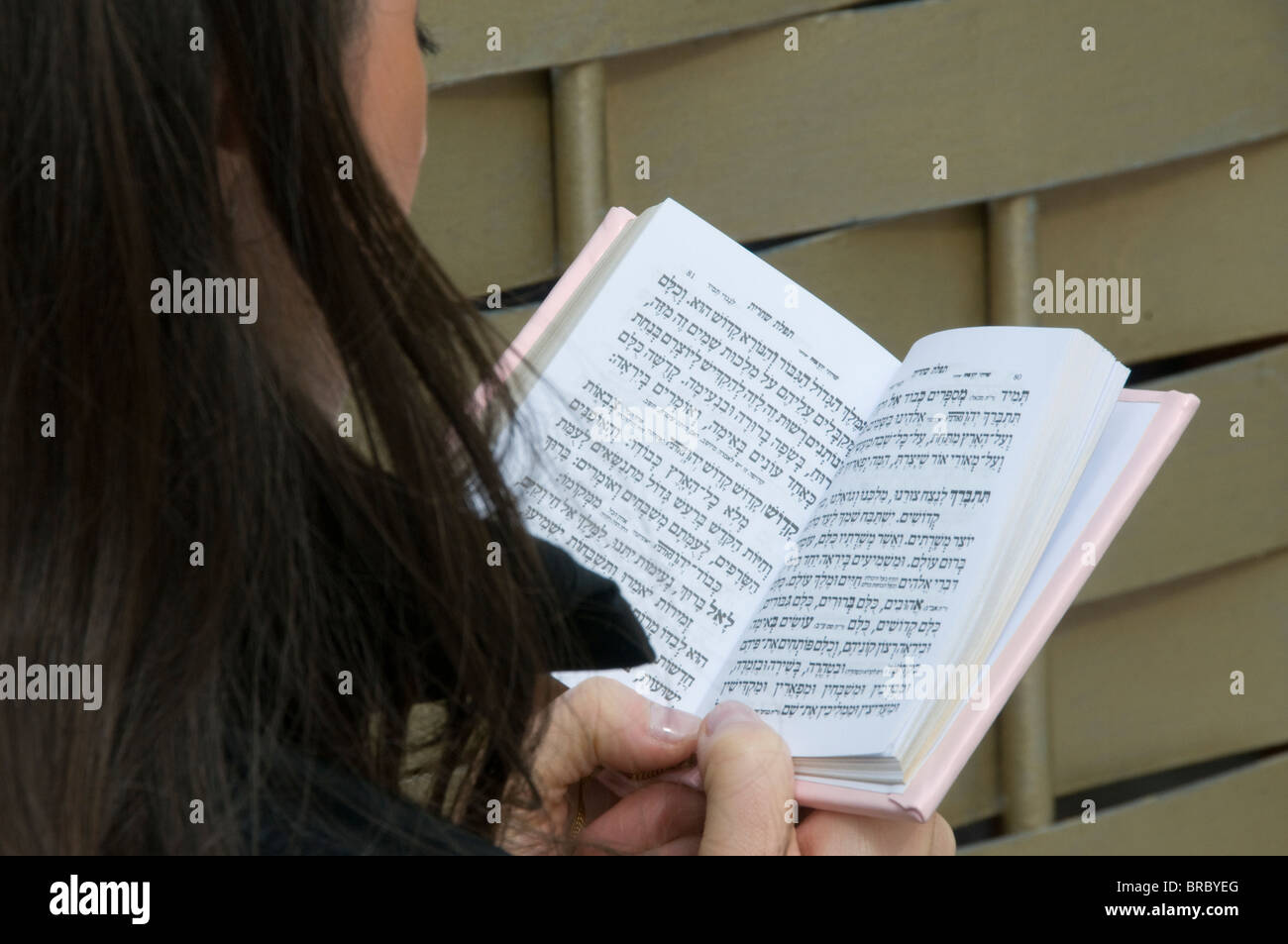 Close up of girl reading Jewish prayer book by the Wailing Wall. - Stock Image