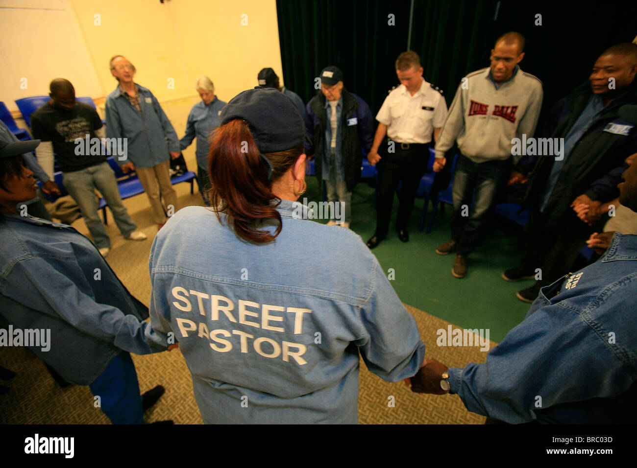 Street Pastors praying with a policeman in North London, London, England, UK - Stock Image