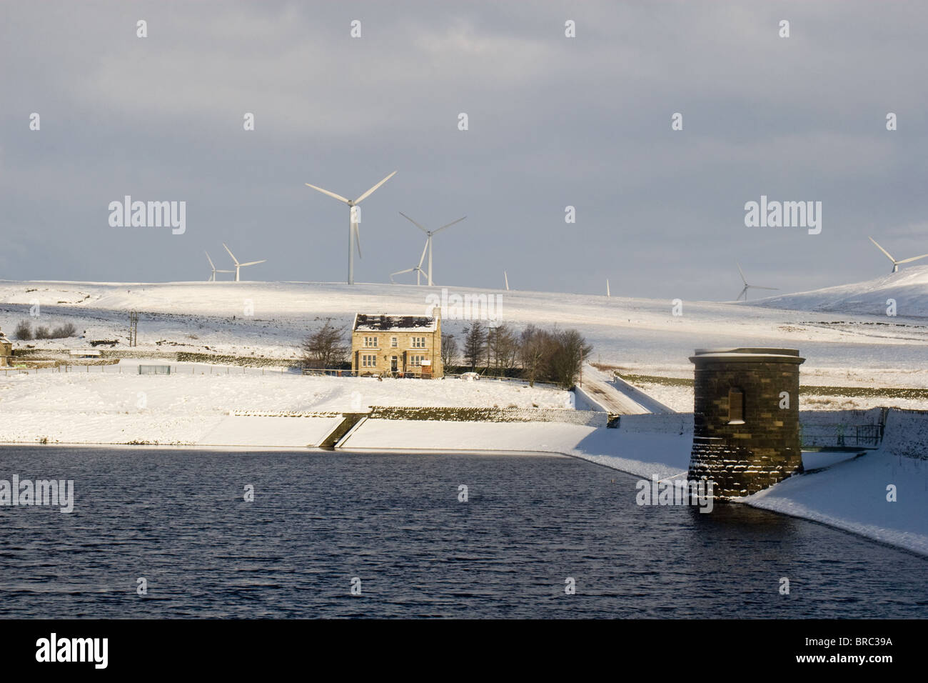 Scout Moor wind turbines, house and Ashworth Reservoir, Lancashire, England, UK - Stock Image