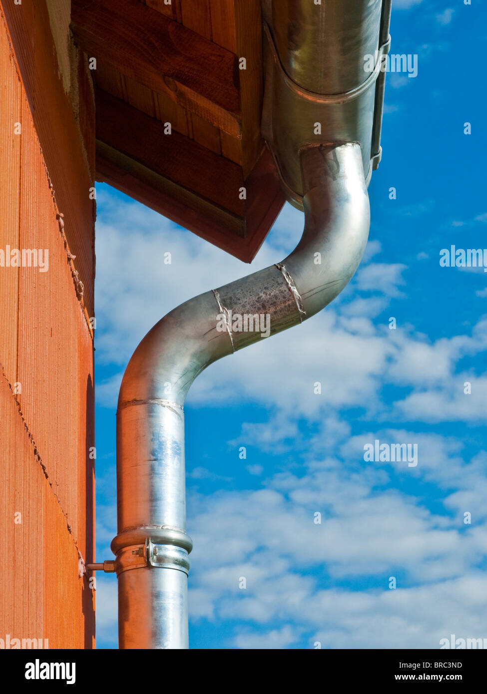 New bungalow construction showing galvanized rainwater gutter and drain-pipe- Indre-et-Loire, France. - Stock Image