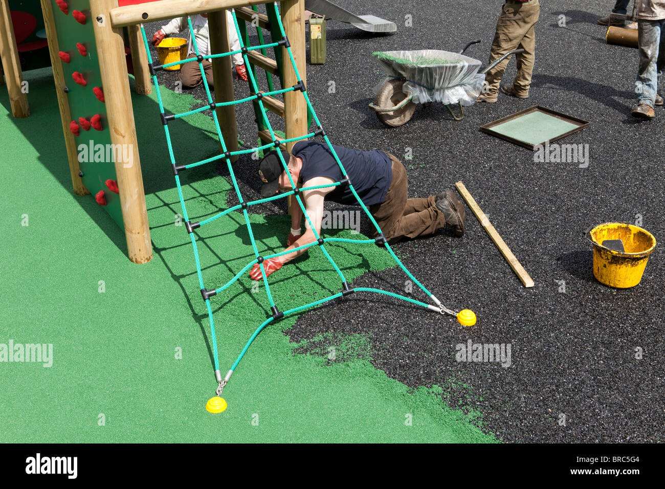 Workmen laying a safety surface on a children's playground in the village of Dent, Cumbria. - Stock Image