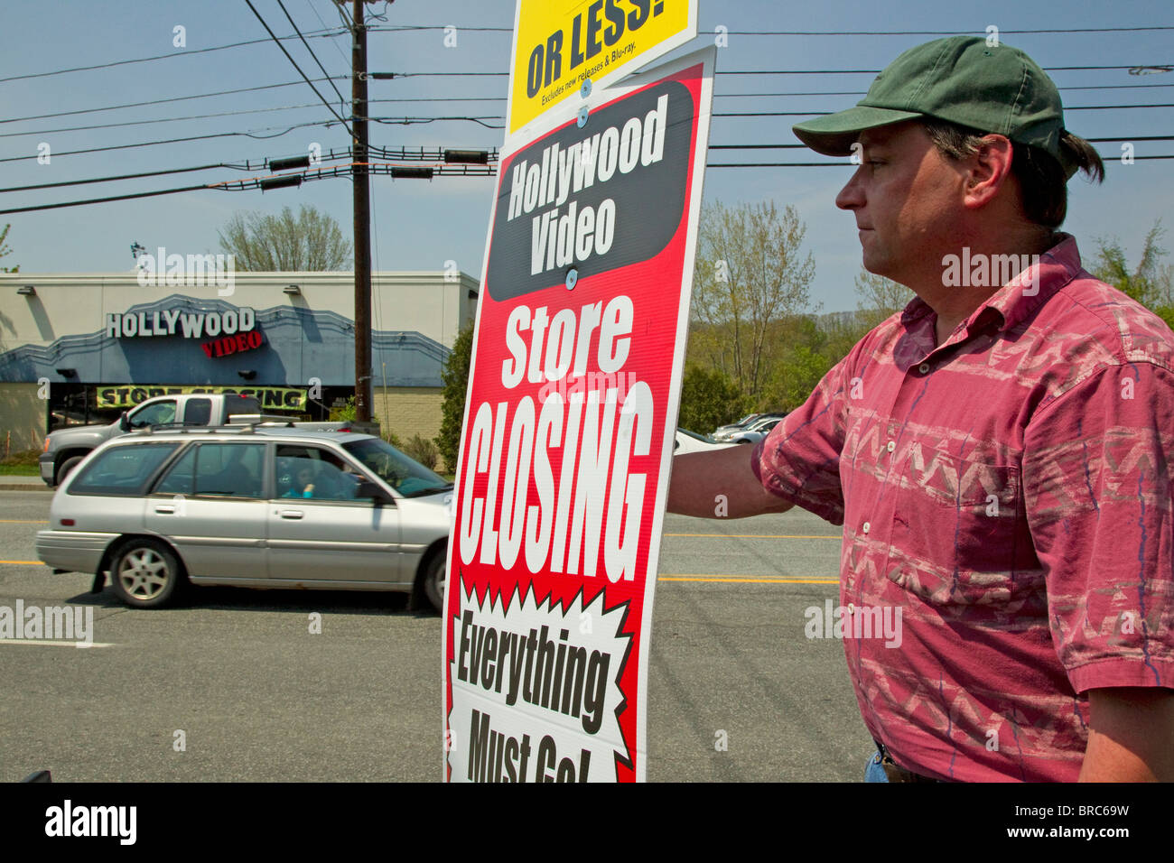 Man holds sign for Hollywood Video Store Closing Going Out of Business Sale - Stock Image