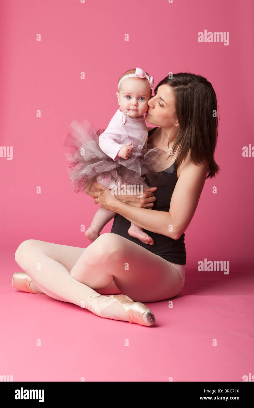 Baby Girl In Tutu Being Kissed By Her Mother, A Ballerina In Pointe Shoes - Stock Image