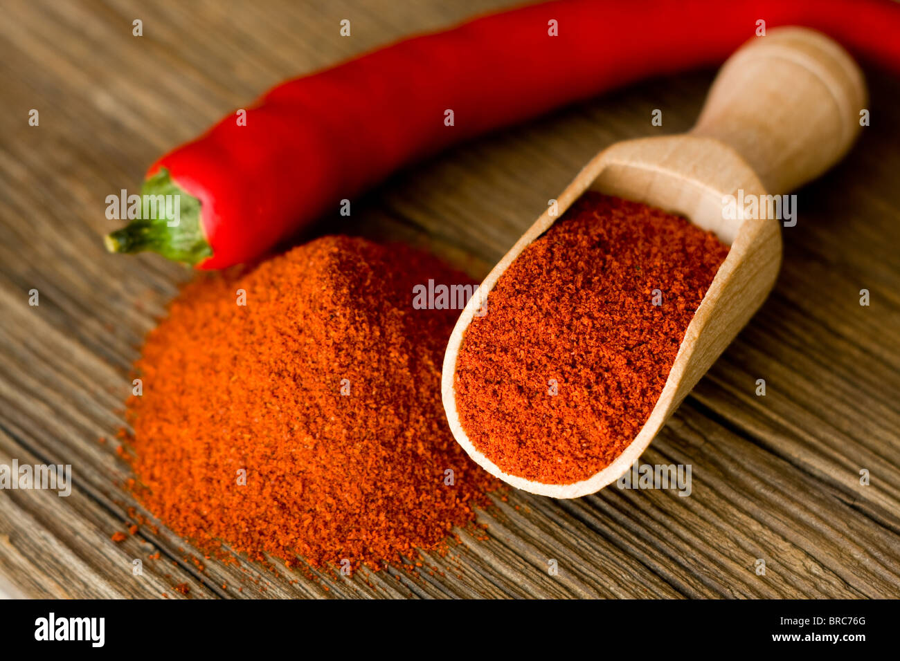 Red hot paprika powder on wooden spoon - Stock Image