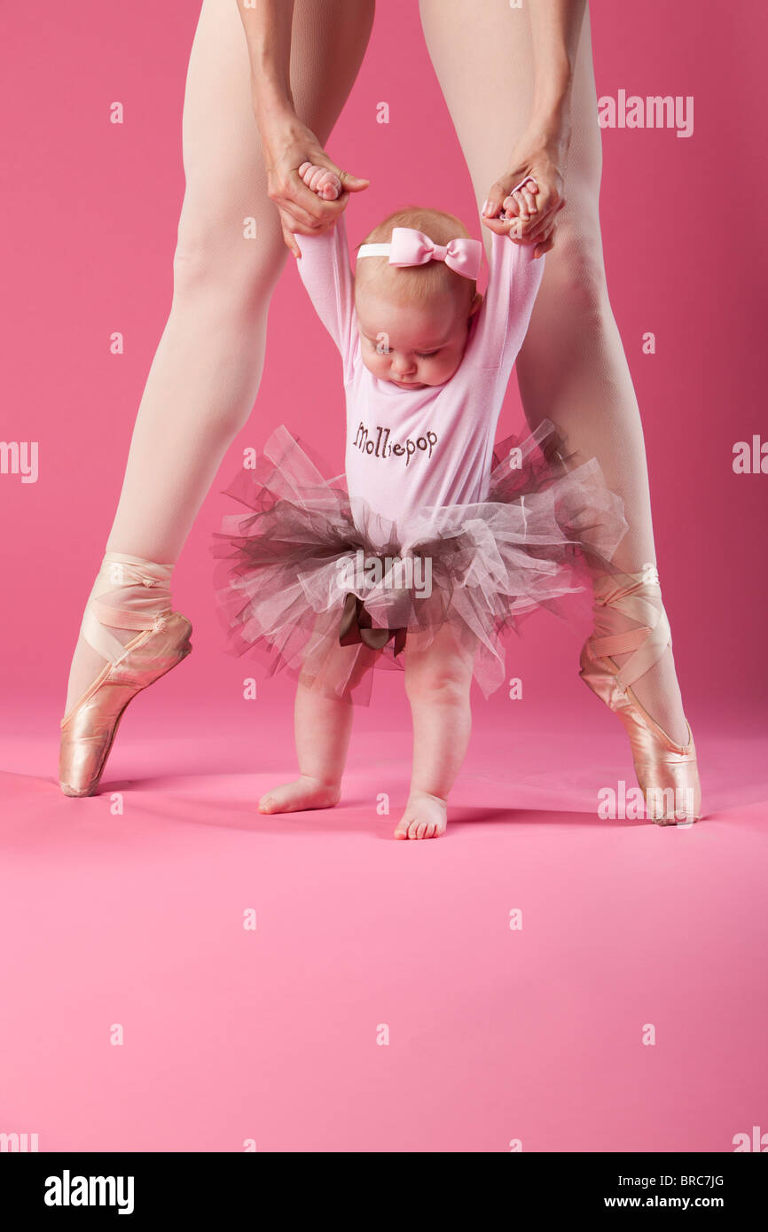 Baby Girl In Tutu With A Ballerina In Pointe Shoes - Stock Image