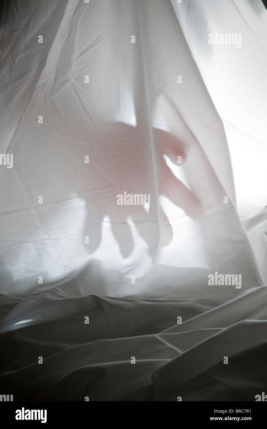 Mysterious Hand Silhouette Behind White Curtain - Stock Image