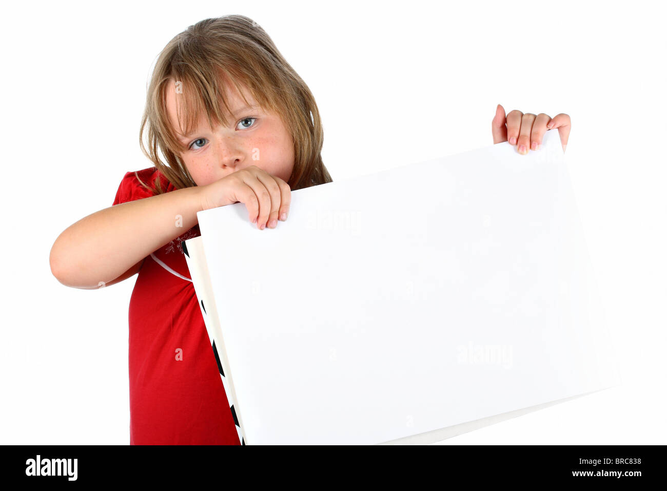 Small girl carrying a blank paper with room for text isolated on white - Stock Image
