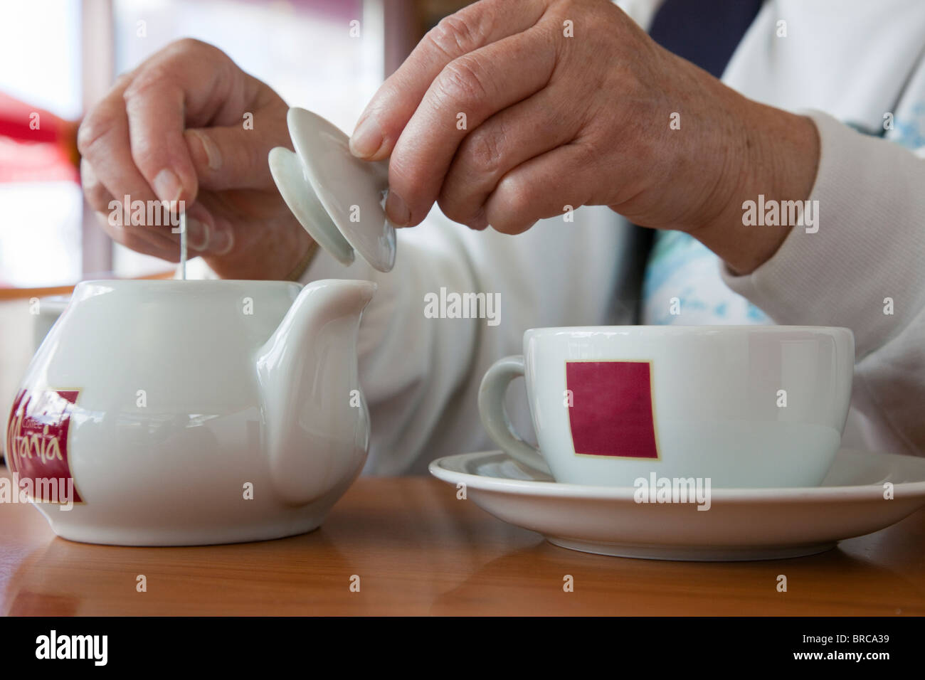 Person in a Coffee Mania café stirring tea in a teapot with a cup and saucer. UK, Britain. - Stock Image