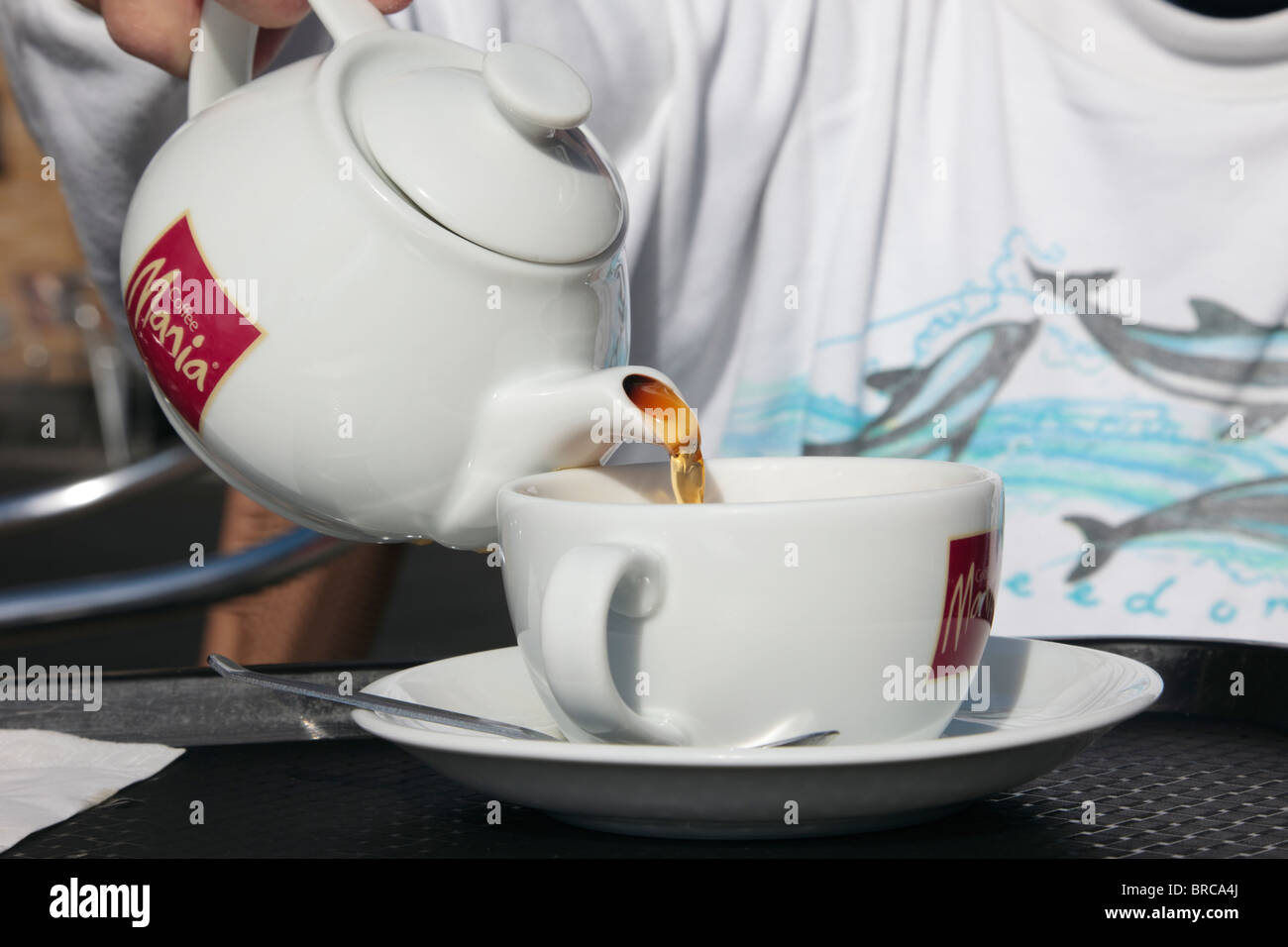Person in a Coffee Mania café pouring tea from a teapot into a cup and saucer. UK, Europe. - Stock Image