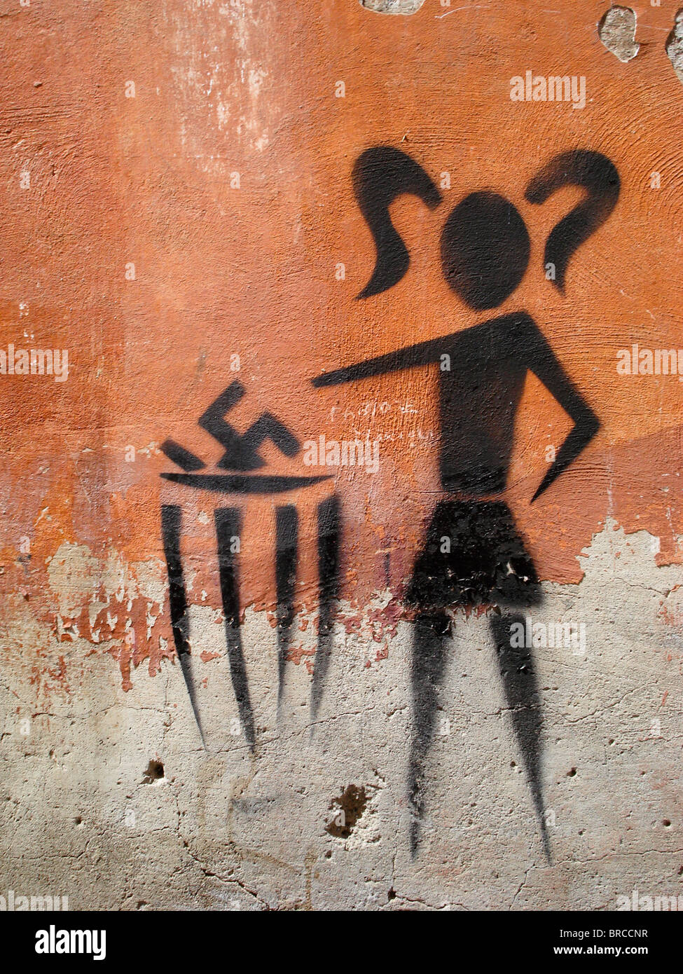 Anti Nazi graffiti on a wall in Rome, Italy - picture depicts girl throwing swastika into a bin. Stock Photo
