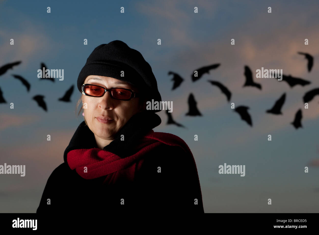 The lonely woman against the dark sky and bats - Stock Image