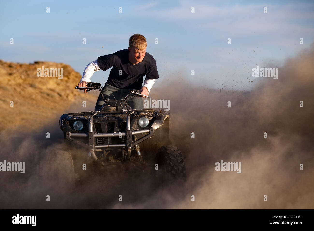 teen with funny expression on quad / ATV - four wheeler kicking up dust - Stock Image