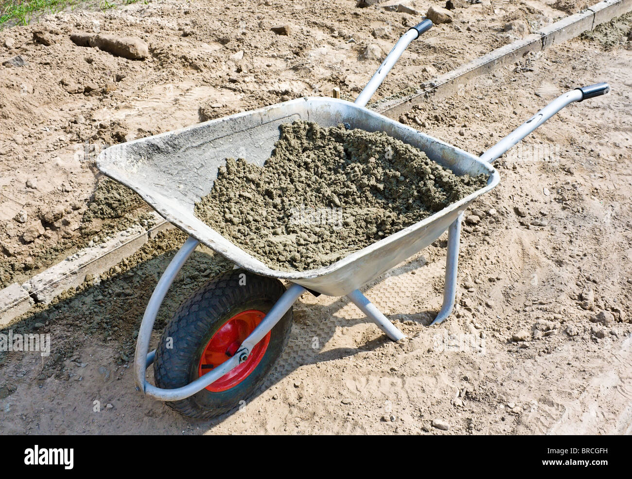 Wheelbarrow with mortar on road construction - Stock Image