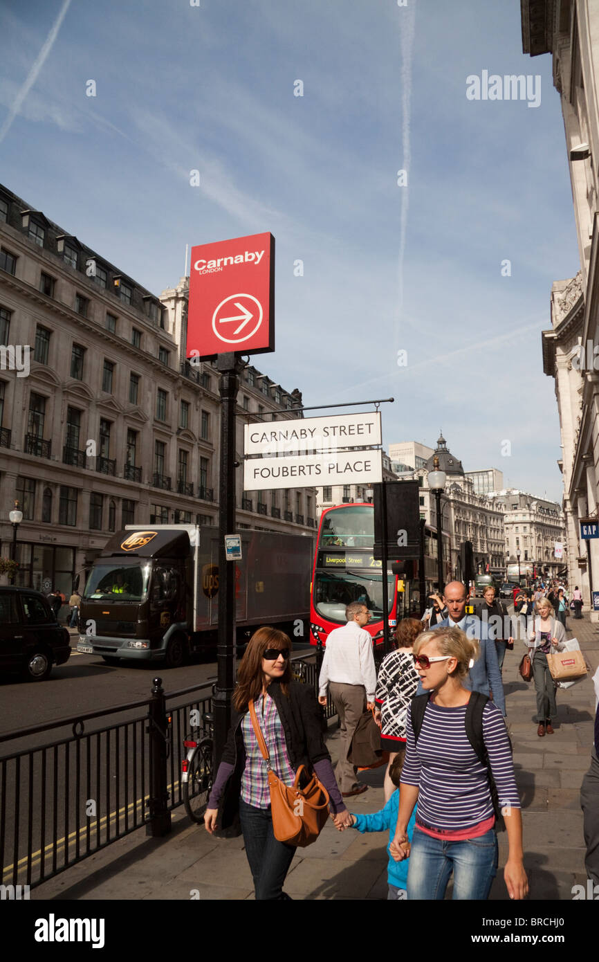 Tourists and shoppers walking on Regent Street, London, England, UK - Stock Image