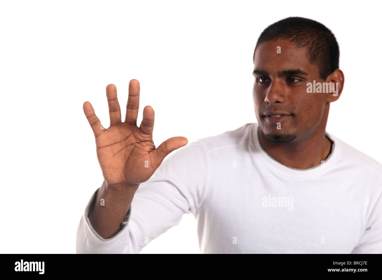 An attractive dark-skinned man pushing with his forefinger. Image with extra copy space. Focus lies on hand. - Stock Image