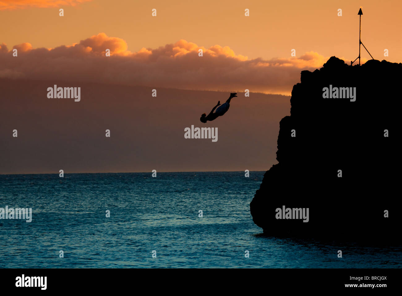 Cliff diver at sunset, Hawaii - Stock Image