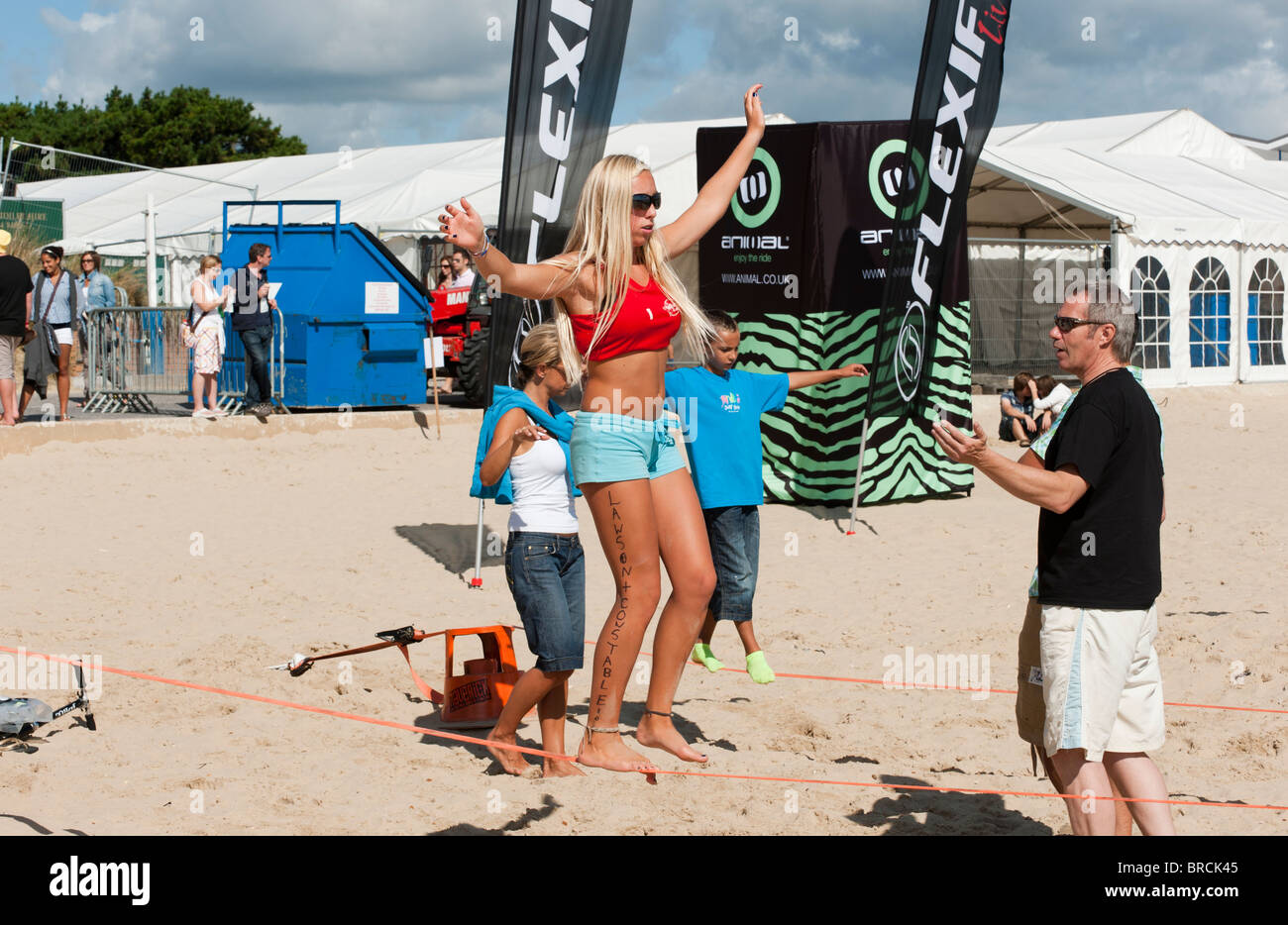 Girl particpating in slacklining at Animal Windfest 2010, held at Sandbanks, Poole. - Stock Image