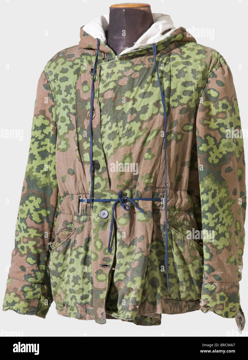A reversible winter jacket of the Waffen SS, with spring camouflage pattern Thickly lined winter jacket with hood, - Stock Image