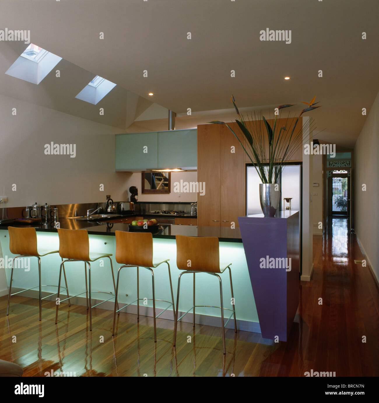 Stools at breakfast bar with lighting behind opaque panel in ...