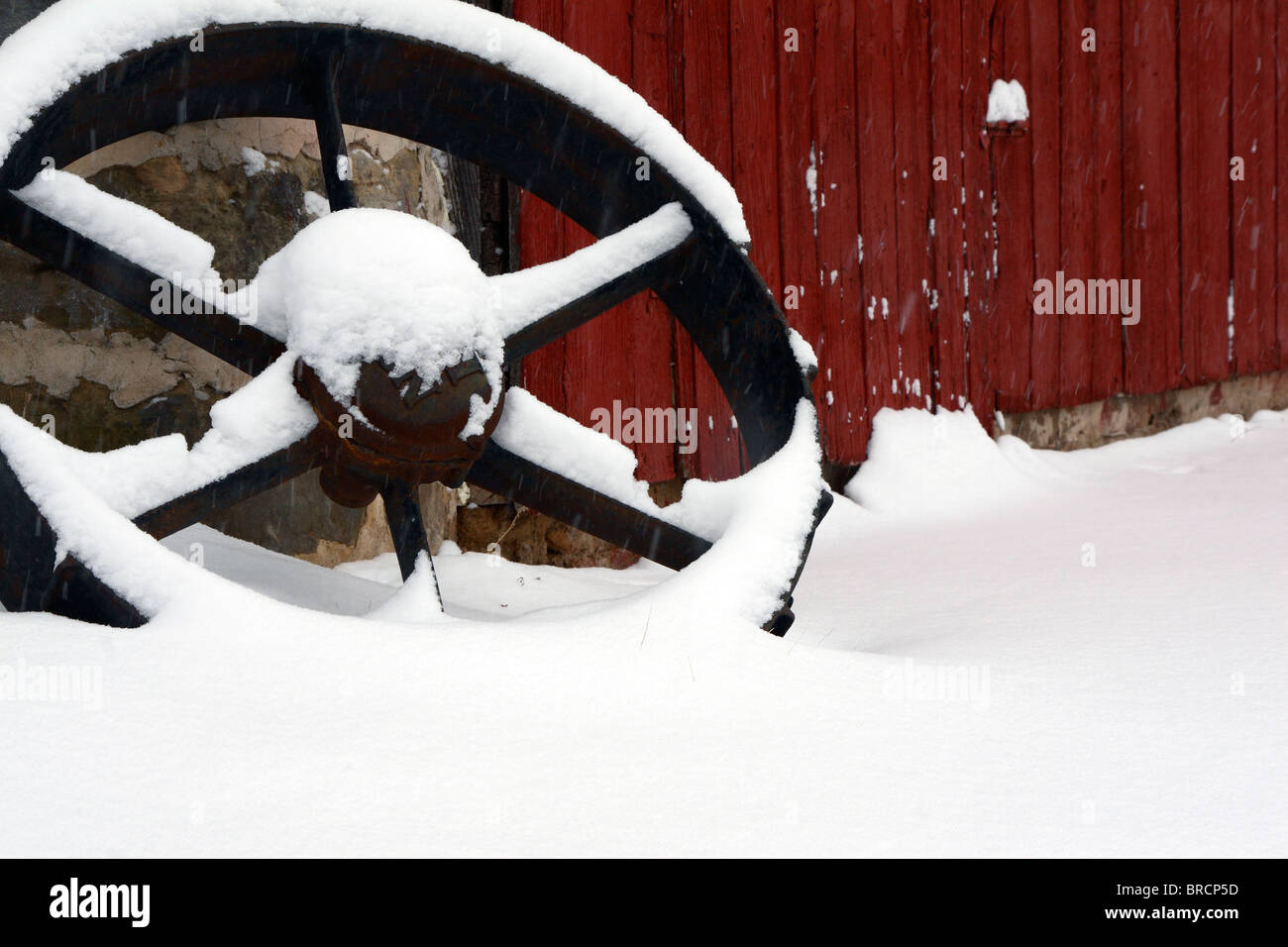 Old Tractor Wheel on Wisconsin Farm in Snow - Stock Image