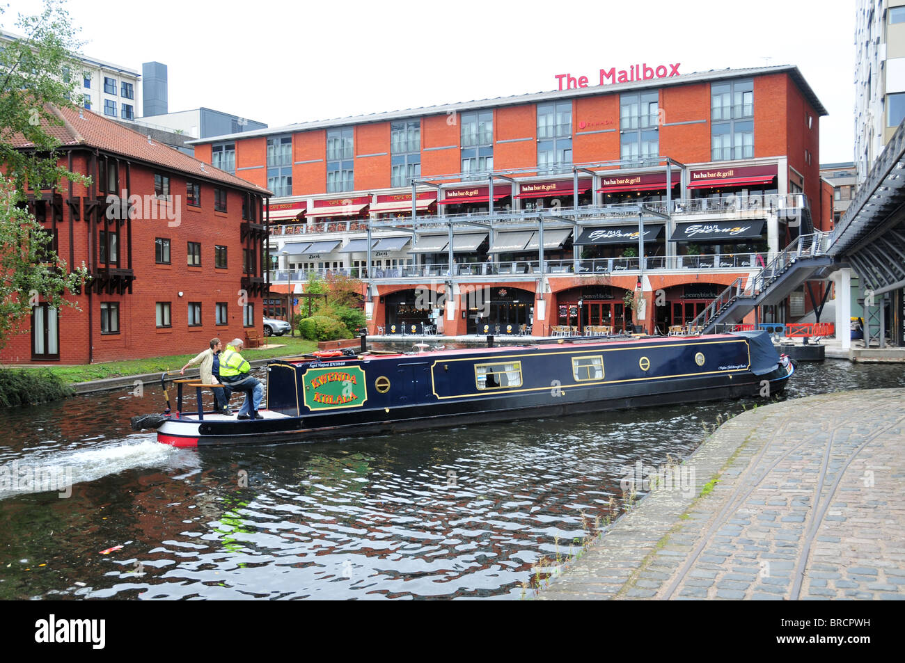 Narrowboat on Birmingham Canal passing to rear of The Mailbox Centre - Stock Image