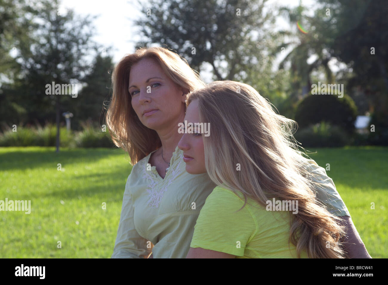 Mother and daughter have a walk at the park, mother looks worried - Stock Image