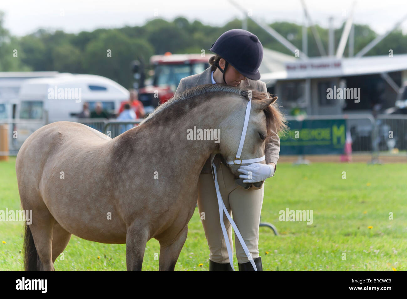 Pretty young woman hugging her pony as they compete in a horse show in  rural England 86d822a5372c