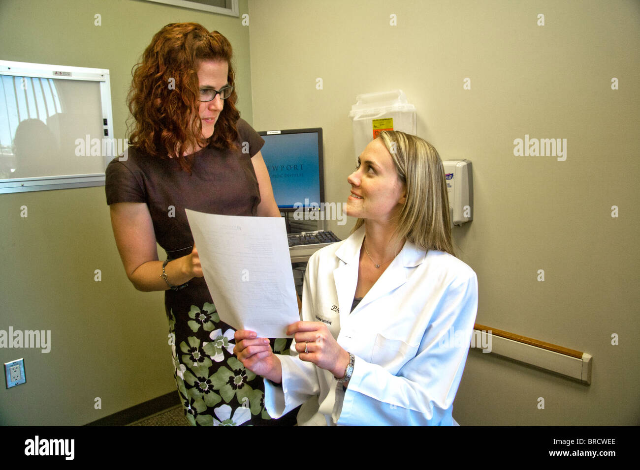 A doctor and her patient read a document of mutual interest at a Newport Beach, CA, medical clinic. MODEL RELEASE - Stock Image