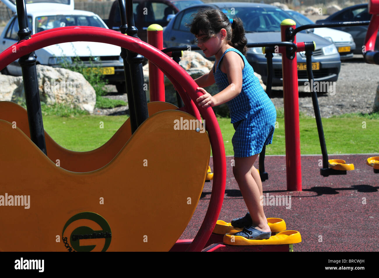 Israel, Haifa, Girl of 6 plays in a public fitness playground - model release available Stock Photo