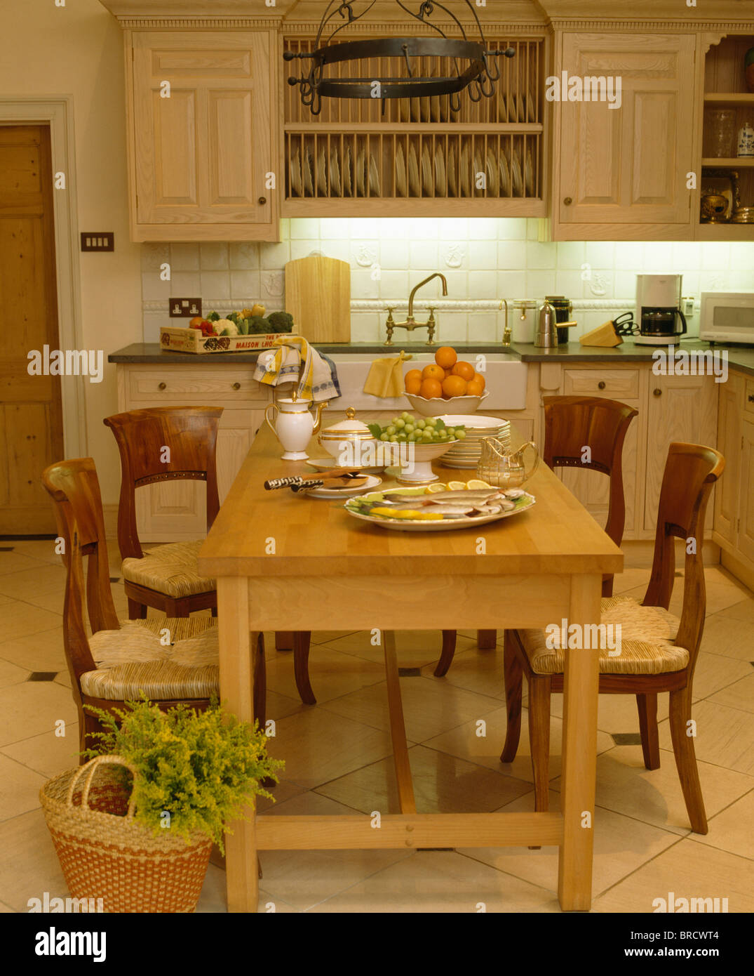 Pale wood table and antique chairs in traditional country kitchen with recessed lighting below fitted wall cupboard - Stock Image