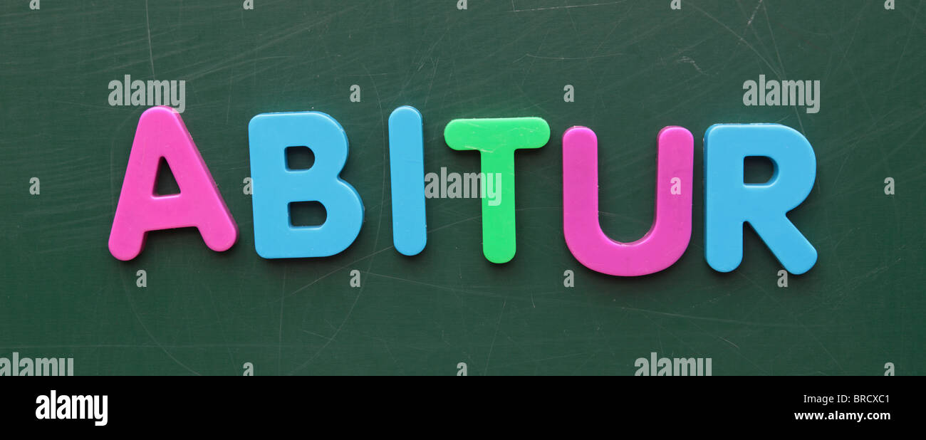 The german term for high-school diploma in colorful letters on a blackboard. - Stock Image