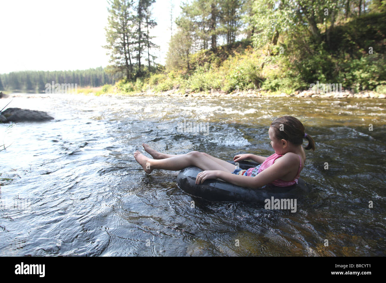 young girl floating down river in inner tube - Stock Image