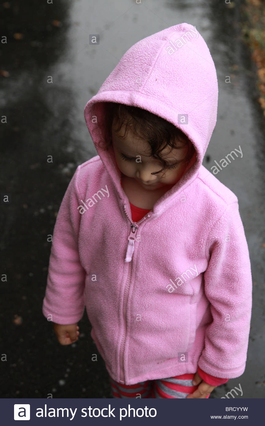A 2 year old girl standing in the rain and wearing a pink hoodie. - Stock Image