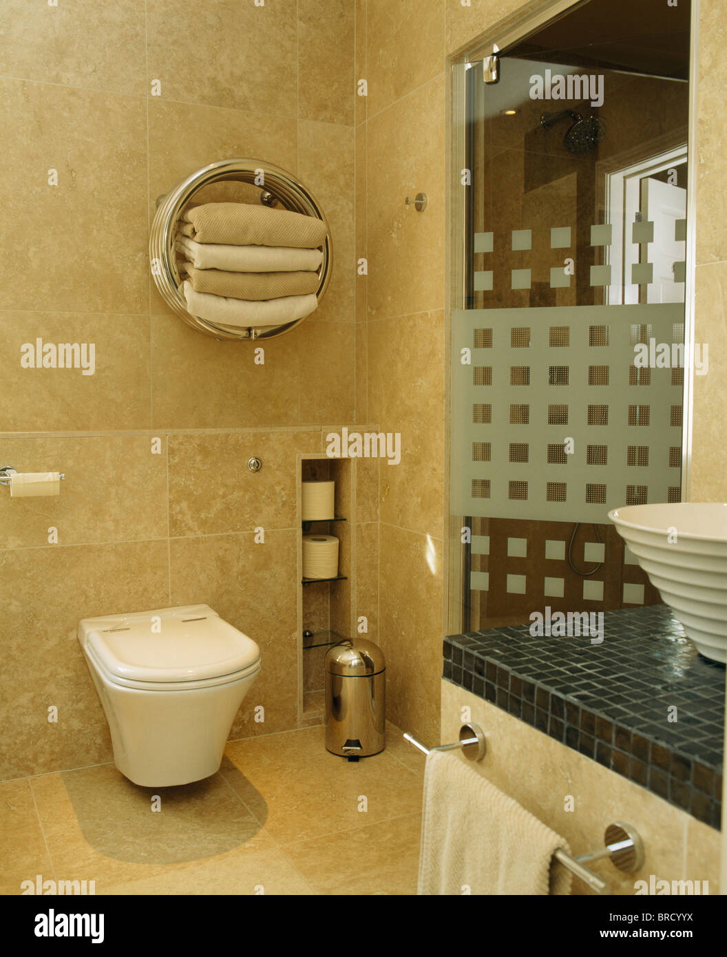 Towels in circular chrome shelf unit above toilet in modern Stock ...