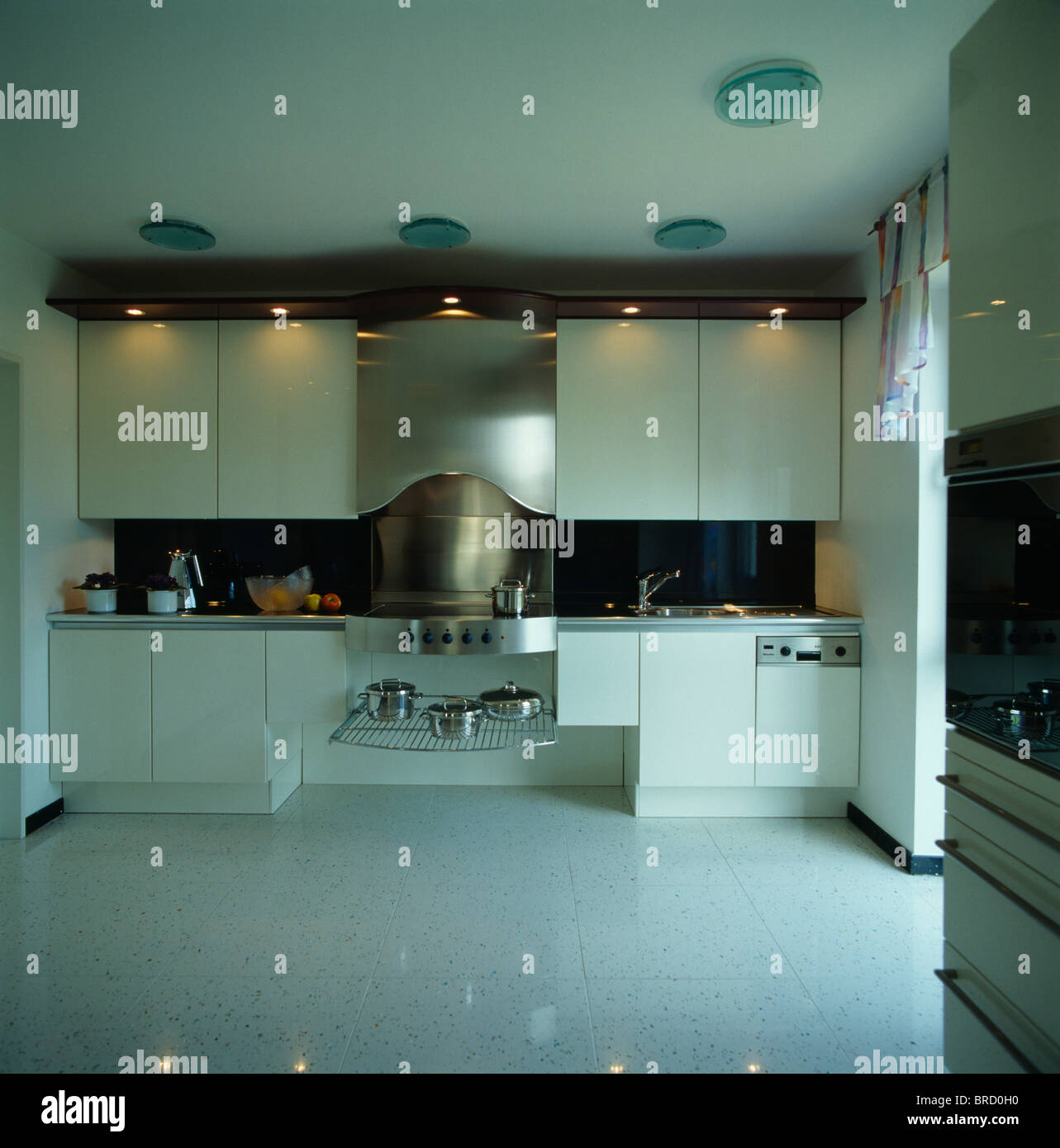 Recessed lighting above cupboards in modern white kitchen with pale ...
