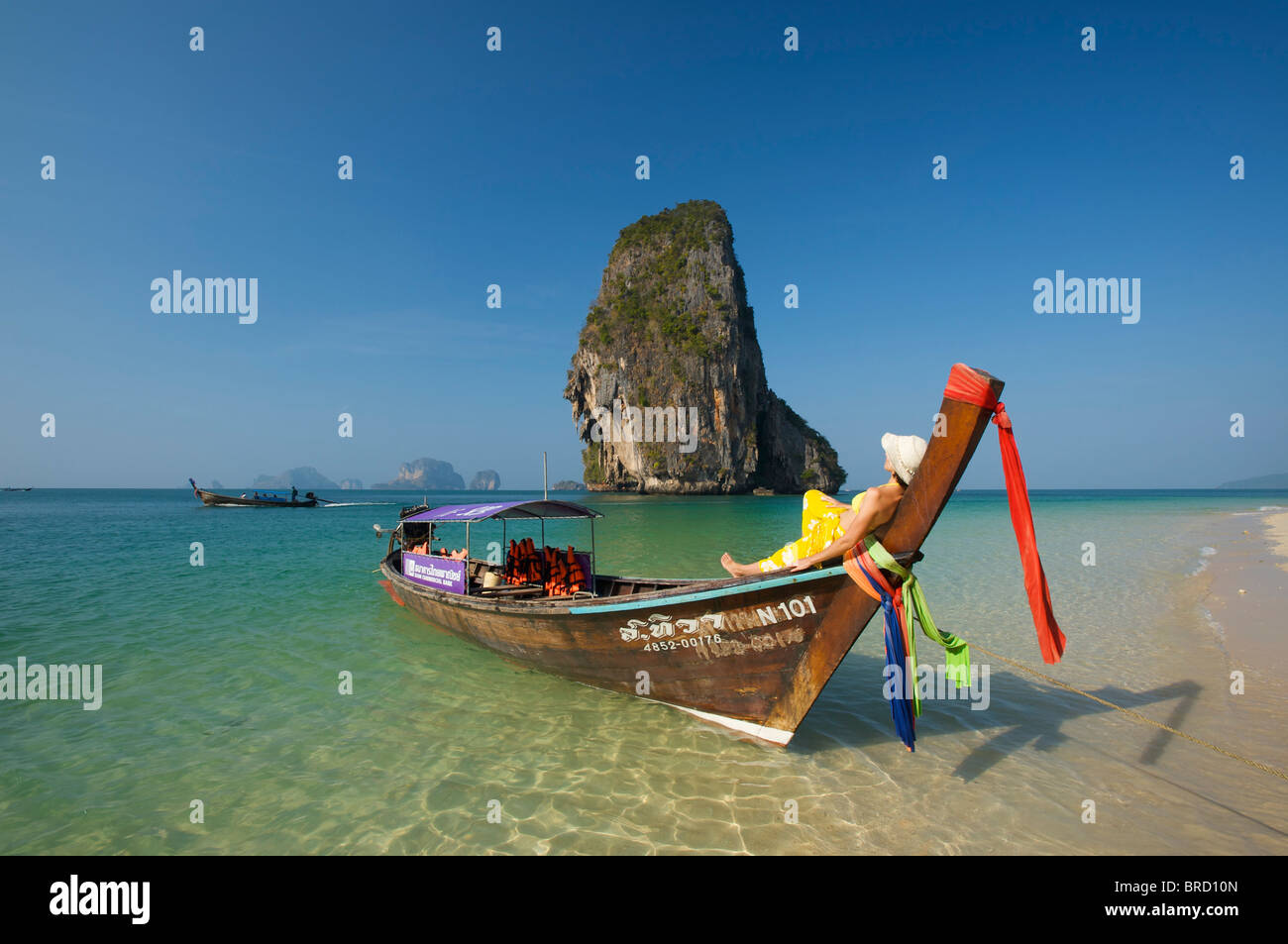Woman relaxing on a long-tail boat at Laem Phra Nang Beach, Krabi, Thailand - Stock Image