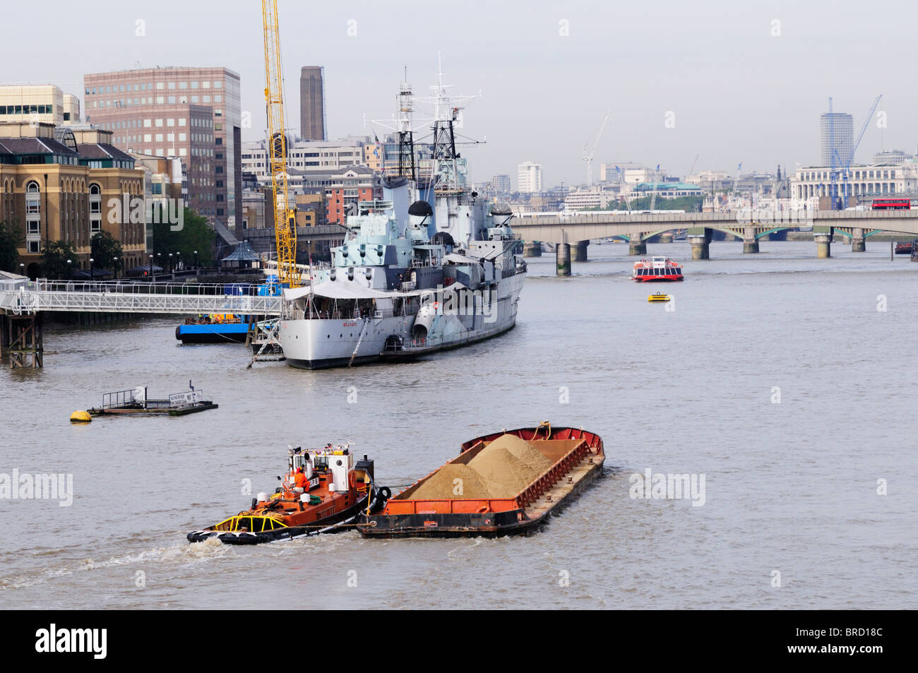 A Barge loaded with Sand being towed up the River Thames, London, England, UK - Stock Image